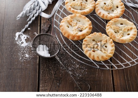 Christmas fruit mince pies on a cooling rack over rustic wooden background  - stock photo