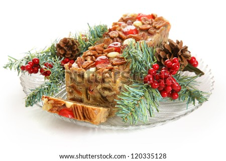 Christmas fruitcake on a glass platter, with pine garnish.  White background.
