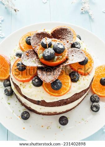 Christmas fruitcake with whipped cream and fruits. Shallow dof.  - stock photo