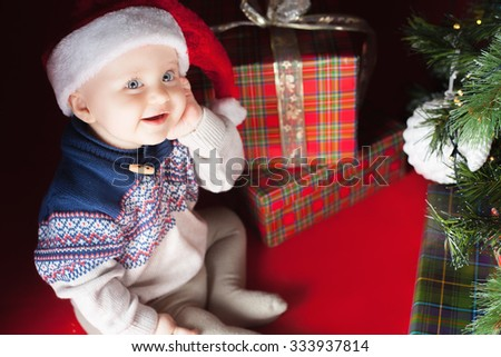 Christmas funny baby wearing a Santa Claus hat sitting near present or gift box! Looking at camera. Night, xmas eve, surprise. Christmas tree. - stock photo