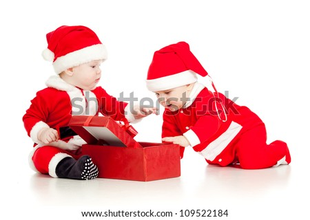 Christmas funny small kids in Santa Claus clothes with gift box - stock photo