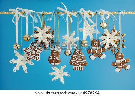 Christmas garland decorated with gingerbread, crocheted snowflakes and golden bells on a blue background. - stock photo