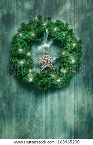 Christmas garland with twinkling lights hanging on rustic door - stock photo