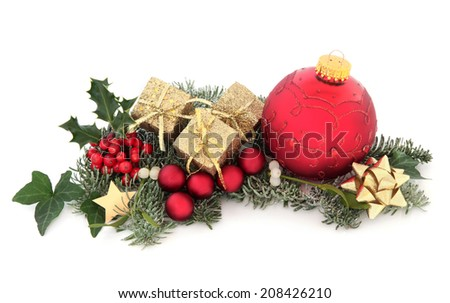 Christmas gift and bauble decorations with holly, ivy, mistletoe, fir and cedar leaf sprigs over white background. - stock photo