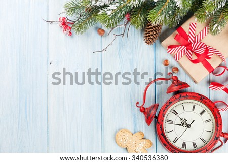 Christmas gift box, alarm clock and fir tree branch on wooden table. Top view with copy space - stock photo