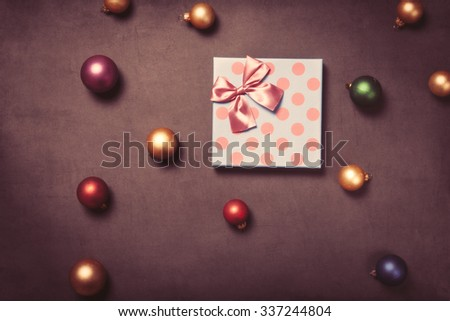 Christmas gift box and baubles on grey background - stock photo