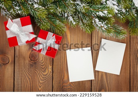 Christmas gift box and blank photo frames over wooden background with snow fir tree - stock photo