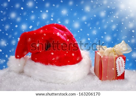 christmas gift box and santa red hat lying on snow against blue background