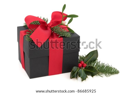 Christmas gift box decorated with red satin ribbon and bow with mistletoe, blue pine fir, holly leaf and berry sprig isolated over white background. - stock photo