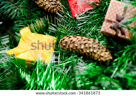 Christmas gift box in the branches of a Christmas tree with Christmas toys on a wooden table close up.horizontal photo