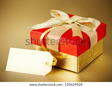 Christmas gift box on gold background - stock photo