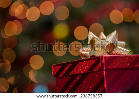 Christmas gift box under a tree with defocused lights and copy space