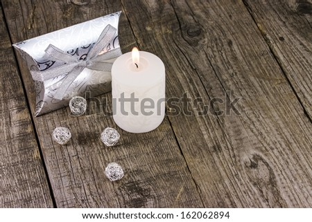 Christmas gift box with candle on wooden background - stock photo