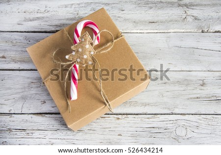 Christmas gift box with candy cane on top. Horizontal studio shot