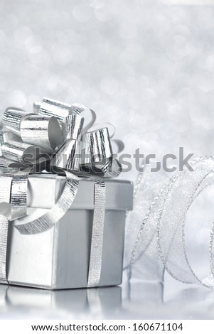 Christmas gift box with decoration on shiny background