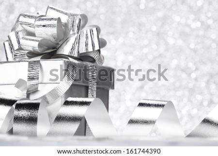 Christmas gift box with decoration on shiny background - stock photo
