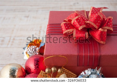 Christmas gift box with decorations and color ball on vintage white wood background