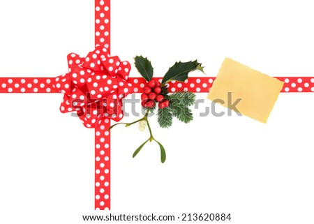 Christmas gift box with red polka dot ribbon and bow, gift tag, holly, fir leaf sprig and mistletoe over white background.  - stock photo