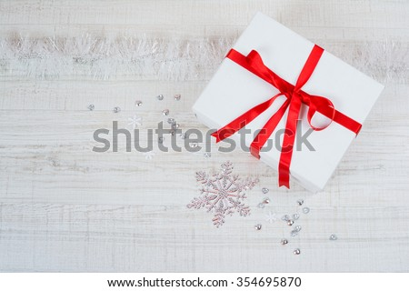 Christmas gift box with red ribbon. Closeup high angle view of big white box wrapped with red ribbon, with decorations around it on white wooden background. - stock photo