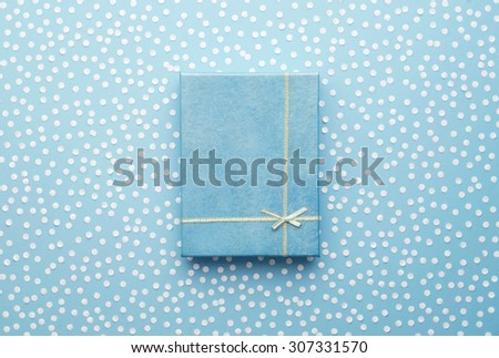 Christmas Gift Box with snow confetti over blue background, above view - stock photo
