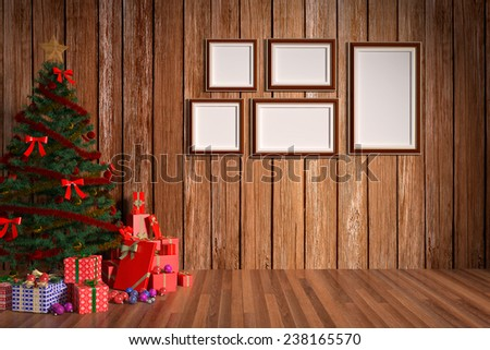 Christmas gift boxes and blank frames in wooden room - stock photo