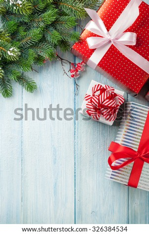 Christmas gift boxes and fir tree branch on wooden table. Top view with copy space - stock photo
