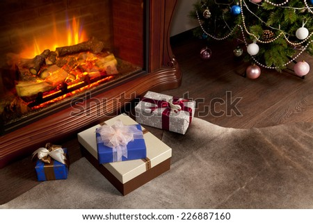 Christmas gift boxes and New Year tree in the interior with fireplace - stock photo