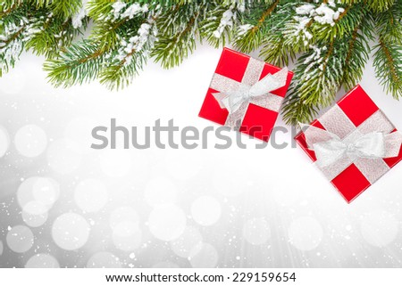 Christmas gift boxes and snow fir tree over bokeh background with copy space - stock photo