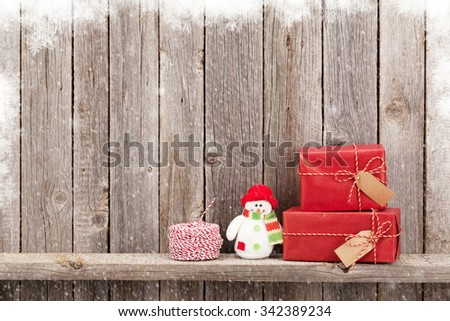 Christmas gift boxes and snowman toy in front of wooden wall. View with copy space - stock photo