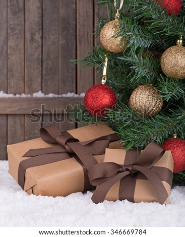 Christmas gift boxes by a decorated tree with wood fence background