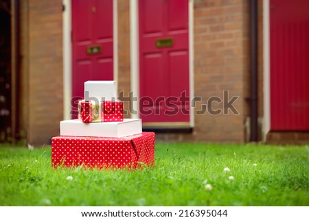 Christmas gift boxes delivered to house front door in summer. Early Christmas preparation concept.  - stock photo