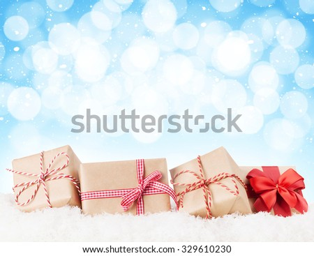 Christmas gift boxes in snow with bokeh background for copy space - stock photo