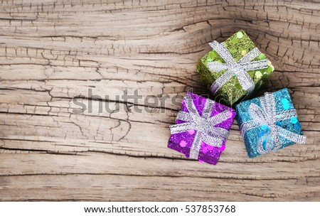 Christmas gift boxes over grunge wooden background. Macro