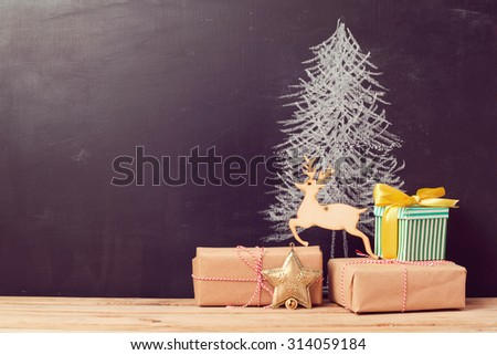 Christmas gift boxes under tree drawing on chalkboard. Alternative Christmas tree background - stock photo