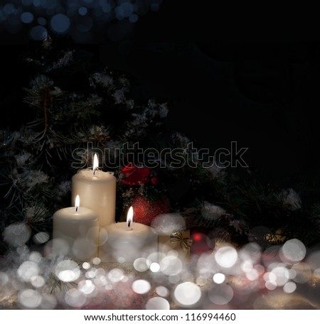 Christmas gift boxes with burn candles under decorated fir on snow - stock photo