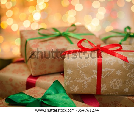 christmas gift boxes wrapped in themed craft paper and satin red and green bow defocused christmas lights background space for copy text - stock photo