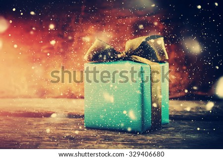 Christmas Gift. Festive Box on Wooden Background with Drawn Snow. Toned - stock photo