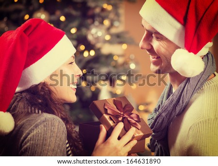 Christmas Gift. Happy Couple in Santa's Hat with Christmas and New Year Gift at Home. Smiling Family Together. Christmas tree  - stock photo
