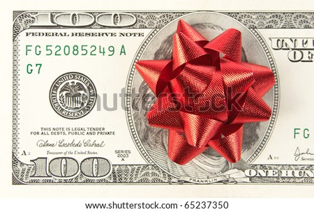 Christmas gift. One hundred bill with red bow - stock photo