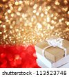 Christmas Gift over red and golden lights background - stock photo