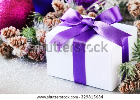 Christmas gift tied with purple satin ribbon with pine cones and shining baubles at the background