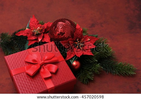 Christmas gift with decorations over red background