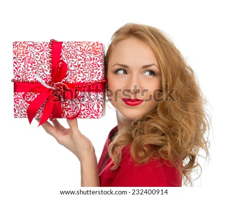 Christmas gift woman with wrapped christmas present smilling happy looking at the corner isolated on a white background - stock photo