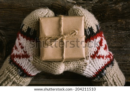 Christmas gift wrapped in brown paper and twine held in hands with mittens - stock photo