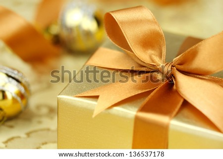 Christmas gift wrapped in golden paper and ties with a decorative golden bow