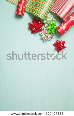 Christmas Gift Wrapping Party Time with Red and Green Colorful Paper and Ribbon Bows on Cyan Blue Shabby Chic Wood Board Background with Room or Space for copy, text, your Holiday Greeting words.
