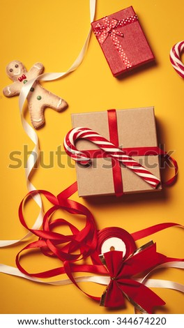 Christmas gifts and candy on yellow background - stock photo