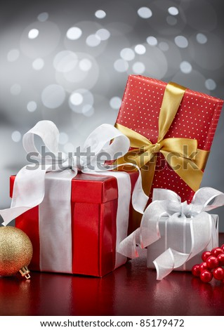 christmas gifts and ornaments against bokeh lights background