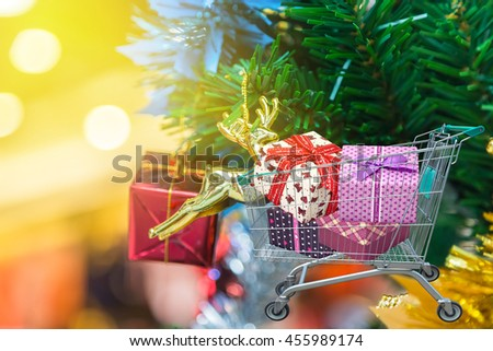 Christmas gifts and presents in shopping trolley with blurred lights on christmas tree background.  - stock photo