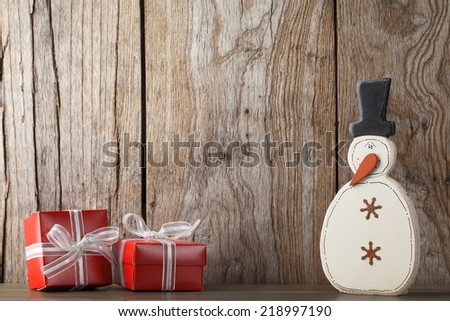 Christmas gifts and snowman on wooden background - stock photo
